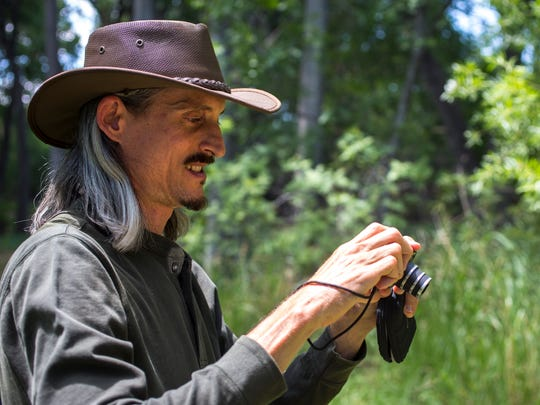 Randy Serraglio, with the Center for Biological Diversity in Tucson, takes a picture of an endangered Chiricahua Leopard frog in the Las Cienega Natural Conservation Area, near Sonoita, on Thursday, July 24, 2014. The area contains the Empire Gulch tributary of Cienega Creek, with several endangered frogs. The area is near the proposed Rosemont Copper mine. According to Serraglio, if the mine begins operation, the water will be drained out of the area, removing the riparian and endangered-animal habitat.