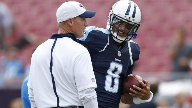 Titans quarterback Marcus Mariota talks to coach Ken Whisenhunt before last Sunday's game against the Buccaneers.