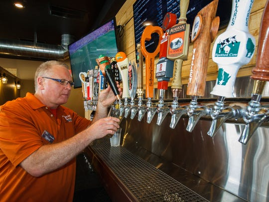Owner Steve Berger taps a pint during the Grand Opening celebration at Beer Snobs Ale & Eats in Hartland in 2016.