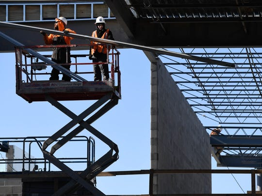 Carl Lennen (left) and Andrew Lennen with Skylight Consultants of America work on installing skylights on the new McCutchanville Elementary School under construction on Petersburg Road Wednesday, January 3. 2018.