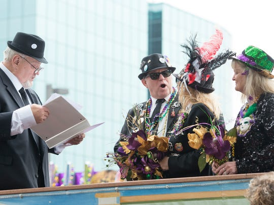 Pat Garber, right, looks on as Pastor Ken McCloskey performs her sister  Brenda Sue Ceccarossi and Robert Stephen Howard's wedding on the Krewe of Blues float before the Mardi Gras parade in Pensacola on Saturday, February 10, 2018.