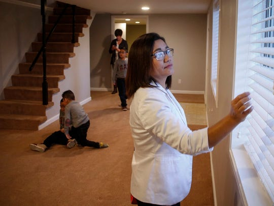 Ester Kiim looks out the window of their finished basement as her children wrestle on the ground prior to moving in. Kim was left a widow after her husband was shot to death after an attempted robbery in April, 2017.
