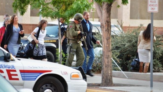 "Albuquerque police in tactical gear escort out Albuquerque City Hall employees on Monday, June 13, 2016, after receiving reports of a possible active shooter and hostage situation in the city building. Albuquerque police spokesman Tanner Tixier said one man was being detained and investigators believed that person was ""the initiator"" who spurred calls from employees inside the building. olice believe the situation may have been the result of a hoax, but they were not taking any chances."