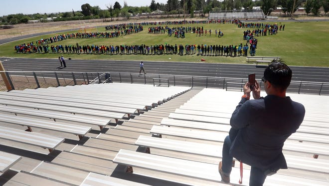 Canutillo Middle School principal Daniel Medina takes a photo of the student body forming a giant puzzle piece on the field Monday.