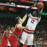 Louisville's Mangok Mathiang grimace as he takes a shot against WKU's Justin Johnson. Mathiang would later leave the game with an injured left foot.
