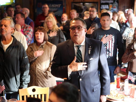 Patrons stand for the singing of the national anthem at Woody's Tavern in Farmingdale, which didn't show football on Nov. 12 as a sign of respect for veterans on Veterans Day weekend.