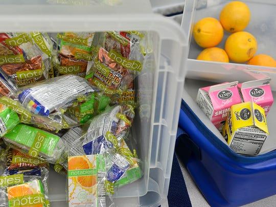 Breakfast packets, milk and oranges line bins Friday,