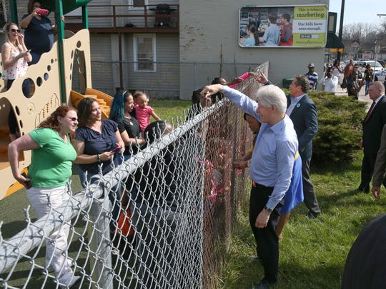 President Bill Clinton reaches over a fence to shake hands as he visits the ABC Head Start on Jefferson Ave.