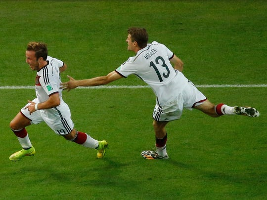 Germany's forward Mario Goetze (L) celebrates with Germany's forward Thomas Mueller after scoring during the 2014 FIFA World Cup final football match between Germany and Argentina at the Maracana Stadium in Rio de Janeiro on July 13, 2014.