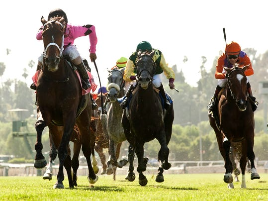 This photo provided by Benoit Photo shows Gary and Mary West's Room Service and jockey Shaun Bridgmohan, left, overpowering Little Journey (Joe Bravo), second from left, and Tiz the Key (Tyler Baze), right, to win the Grade I, $350,000 American Oaks, Saturday, May 31, 2014 at Santa Anita Park in Arcadia, Calif. (AP Photo/Benoit Photo)