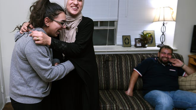 Khuloud Hamzeh, middle, hugs her friend Selwa Kanakrieh in her Nashville home. Kanakrieh has been helping Hamzeh and her husband, Fahed Nakshou, right, with errands as they make Nashville their new home.