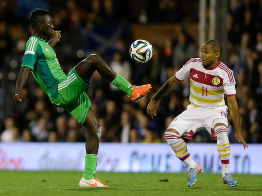 Nigeria's Reuben Gabriel, left, competes for the ball with Scotland's Ikechi Anya during the international friendly soccer match between Nigeria and Scotland at Craven Cottage Stadium in London, Wednesday, May 28, 2014. Nigeria will be in Group F in the upcoming World Cup in Brazil. (AP Photo/Kirsty Wigglesworth)