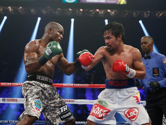 FILE - In this April 12, 2014, file photo, boxers Timothy Bradley, left, and Manny Pacquiao, of the Philippines, face off in their WBO welterweight title fight in Las Vegas. Nearly a year after Pacquiao failed to hurt Floyd Mayweather Jr., the Filipino congressman is preparing for what could be his final fight. Bradley would love to send Pacquiao into retirement when they complete their trilogy on April 9. (AP Photo/Eric Jamison, File)