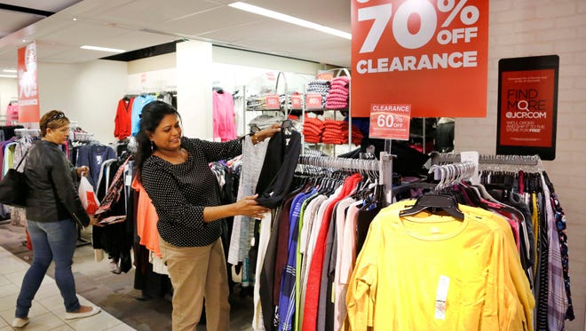 """Indro Rei shops for blouses on clearance in a """"Red Zone"""" at a J.C. Penney store in New York on March 10. Sunnier economic times have stores looking to recapture lost profits."""