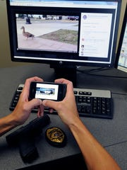 Lt. Brian Krzykowski, Wisconsin Rapids Police Department works via his smartphone monitoring the department's Facebook page, and plays a duckling rescue movie he produced on his office computer Friday.