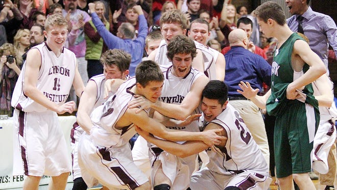 Members of the Lyndon Institute boys basketball team charge the court after its' 56-37 win over Woodstock in the Division II high school boys basketball state championships Saturday at Barre Auditorium.
