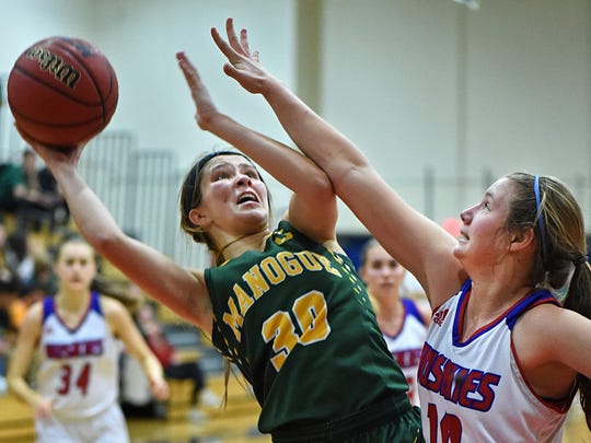 Bishop Manogue's Katie Turner goes up to shoot with Reno's Dominique Harding covering during Thursday's game at Reno High School. Bishop Manogue beat Reno 69-59.
