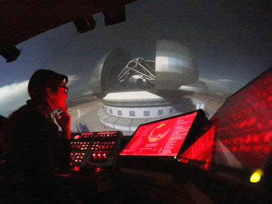 "Evelyn Maldonado, program manager for the Gene Roddenberry Planetarium at 6531 Boeing Drive, in November 2017 watches the console as a program about telescopes titled, ""Two Small Pieces of Glass,"" is projected onto the domed ceiling to middle school students in November 2017."