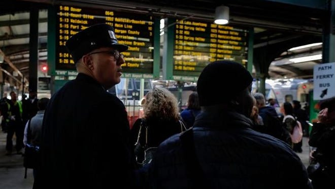 A New Jersey Transit conductor assists a commuter, Wednesday, April 5, 2017, at the Hoboken Terminal in Hoboken, New Jersey. The heads of the two major commuter rail lines that use New York's Penn Station took turns criticizing Amtrak on Wednesday for two recent derailments that continued to cause headaches for commuters in the nation's busiest rail hub.