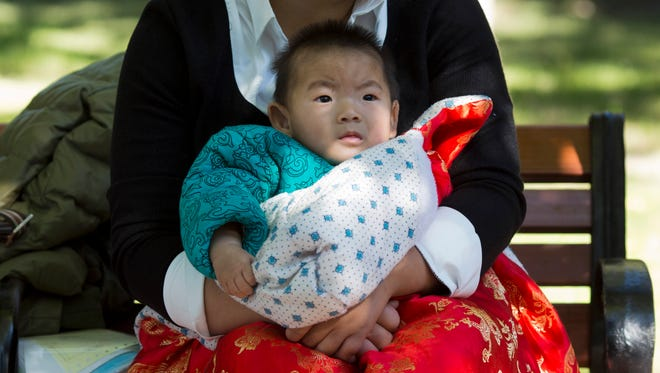 A child is wrapped up against the cold at a park in Beijing, China, Friday, Oct. 30, 2015.