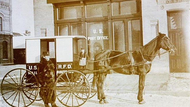 The building in this photograph, circa 1899-1910, is located on the corner of Church and West Wisconsin Avenue. The block was called the Sherry Post Office Block, after Henry Sherry, a wealthy lumberman who put up many of the buildings on the north side of West Wisconsin Avenue. Standing next to the Rural Free Delivery wagon is Postman Bert Cramer.