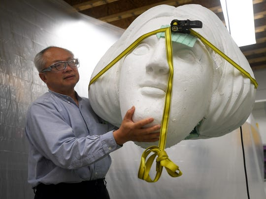 Mel Chin holds the head of what will be a 21-foot-tall