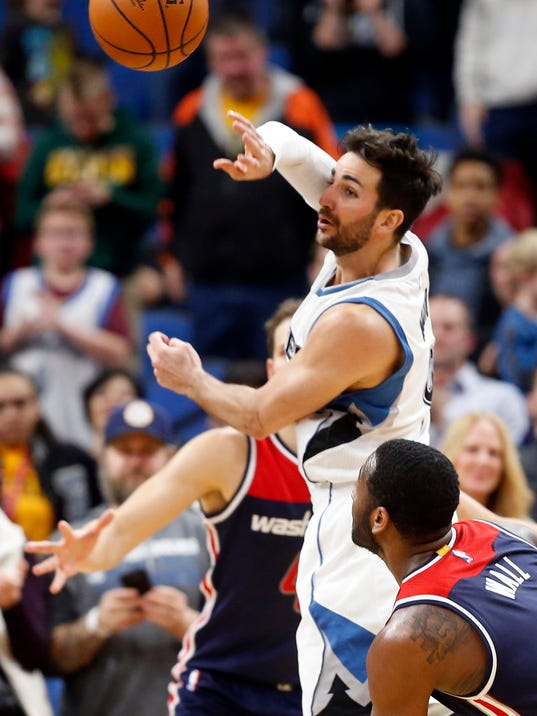 Minnesota Timberwolves' Ricky Rubio, top, of Spain, passes the ball as Washington Wizards' John Wall watches during the second half of an NBA basketball game Monday, March 13, 2017, in Minneapolis. The Timberwolves won 119-104. Rubio set a franchise record with 19 assists. He scored 22 points. (AP Photo/Jim Mone)