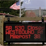A road sign advising the closure of Highway 530 stands in view of a flag still at half-staff Tuesday, April 15, 2014, in Darrington, Wash.