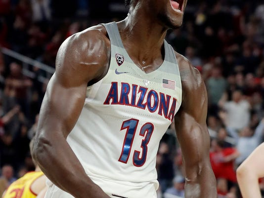 FILE - In this March 10, 2018, file photo, Arizona's Deandre Ayton reacts after a dunk against Southern California during the second half of an NCAA college basketball game for the Pac-12 men's tournament championship, in Las Vegas. Ayton is a member of the Associated Press NCAA college basketball All-America first team, announced Tuesday, March 27, 2018. (AP Photo/Isaac Brekken, File)