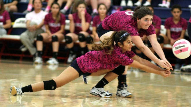 "Lady Cats Julyssa ""Boo"" Ortiz, left, and Nicole Wycoff move in to dig an Onate attack during Thursday's District 3-6A match against the Knights. Onate swept the match, 25-17, 25-14 and 25-16 at Deming High School."