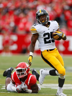Iowa running back Akrum Wadley (25) breaks the tackle of Rutgers defensive back Blessuan Austin (10) during the first half in Piscataway, N.J.