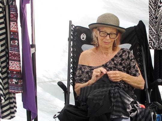 Fabric artist Bonnie Griffth of Burlington works beneath a canopy on Pine Street on Saturday at the South End Art Hop.