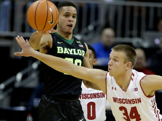 Wisconsin's Brad Davison (34) tries to block a pass by Baylor's Manu Lecomte during the first half of an NCAA college basketball game in the Hall of Fame Classic, Monday, Nov. 20, 2017, in Kansas City, Mo. (AP Photo/Charlie Riedel)