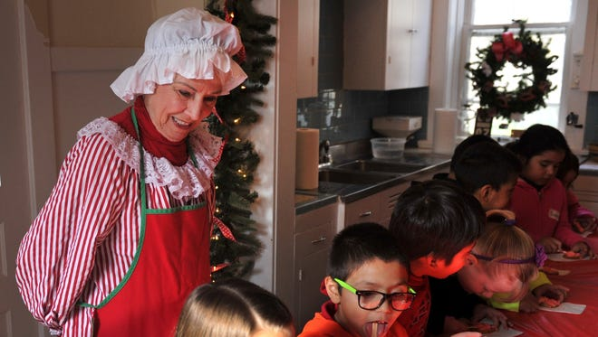 Students from Crockett Elementary make cookies while Mrs. Claus supervises at Santa House in 2015.