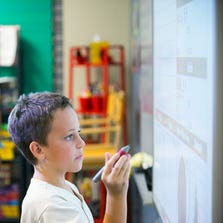 Student Braeden Schneider, 9, works on a math problem in front of his class at Centennial Elementary School, ranked No. 1 among district K-6 schools in Arizona..