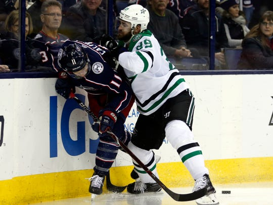 Dallas Stars defenseman Greg Pateryn, right, checks Columbus Blue Jackets forward Matt Calvert during the second period of an NHL hockey game in Columbus, Ohio, Thursday, Jan. 18, 2018. (AP Photo/Paul Vernon)