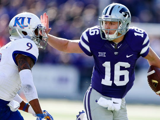 FILE - In this Saturday, Nov. 26, 2016, file photo, Kansas State quarterback Jesse Ertz (16) pushes away Kansas safety Fish Smithson (9) as he makes a long run during an NCAA college football game in Manhattan, Kan. Kansas State plays TCU in Fort Worth, Texas, Saturday, Dec. 3. (Bo Rader/The Wichita Eagle via AP, File)