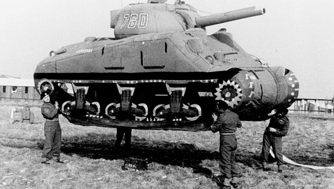 Soldiers in the Ghost Army move an inflatable dummy tank into position.