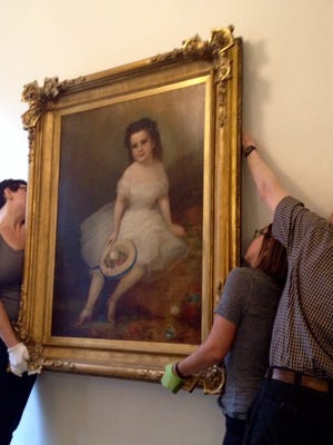 Filson Historical Society president and CEO Craig Buthod, helps preparator Amanda Briede, second from right,  and intern Andrea Truitt hang a painting at the society's renovated and expanded campus, 1310 S. Third St. in Old Louisville.