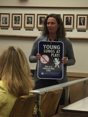 "Holly Dolan, director of education and outreach for Lebanon Family Health Services, shows Lebanon City Council one of the ""Young Lungs At Play"" signs the organization is donating to the city for placement at city-owned playgrounds."