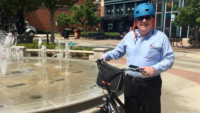 Carmel Mayor Jim Brainard  displays an electric-powered bike at Clay Terrace on Aug. 25, 2017.