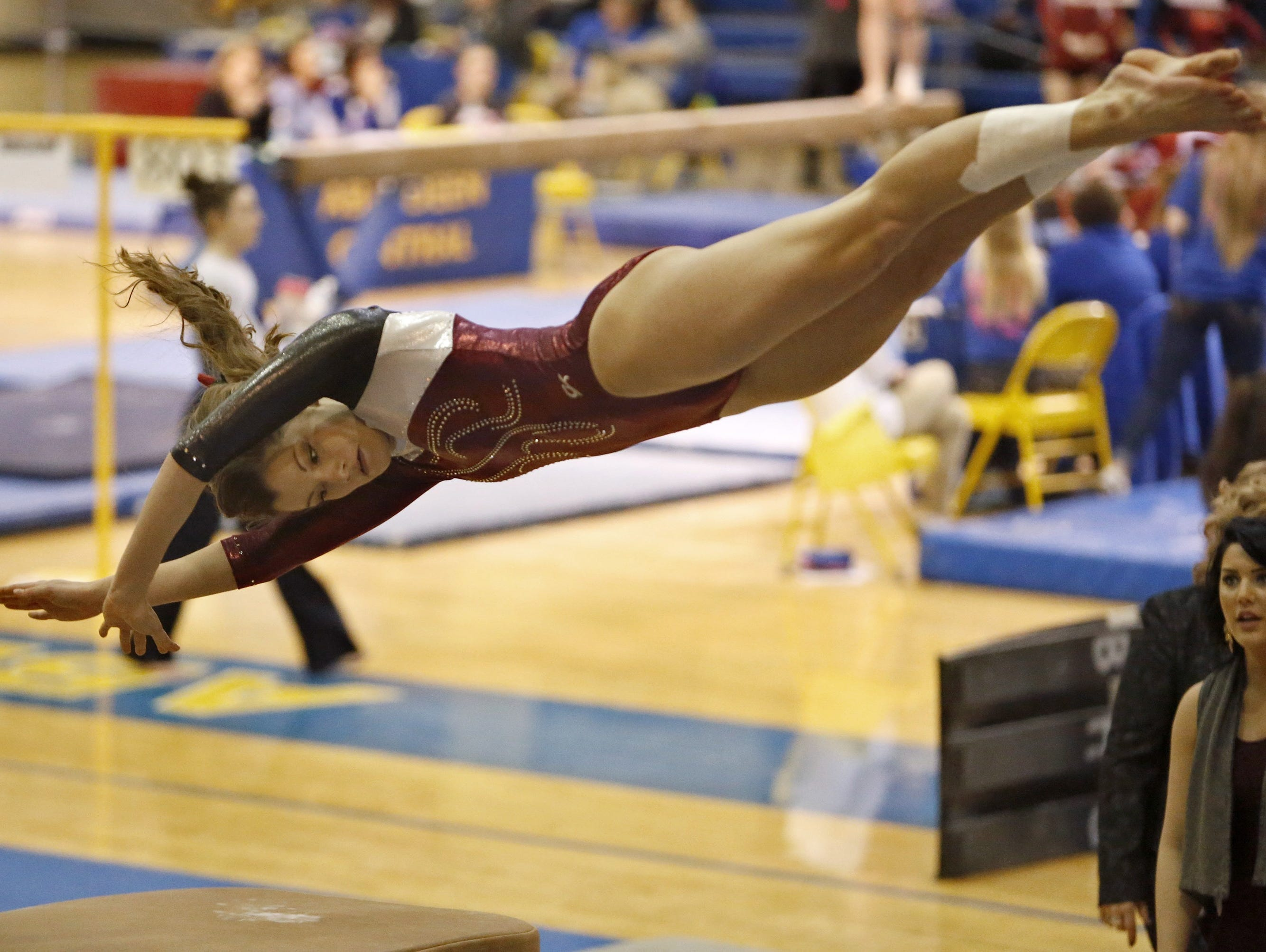 Madison's Jenni Giles spins off the vault Friday at the Class A State Gymnastics Meet at the Golden Eagles Arena.