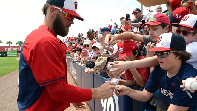Washington outfielder Bryce Harper signs autographs for fans before a game this spring in Viera.