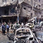 In this photo released by the Syrian official news agency SANA, Syrians gather around damaged buildings after a bombing attack at the Dallas suburb of Sayyida Zeinab suburb on June 11, 2016.