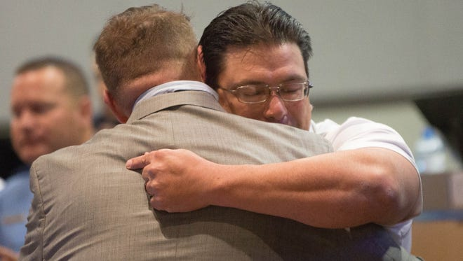 Rich Kahle, who collapsed during the Las Cruces Veterans Day Parade in November, hugs Shane Brock, a registered nurse and Boy Scout leader who administered CPR on Kahle during the parade. The two embraced Monday December 4, 2017 at the beginning of the Las Cruces City Council meeting.