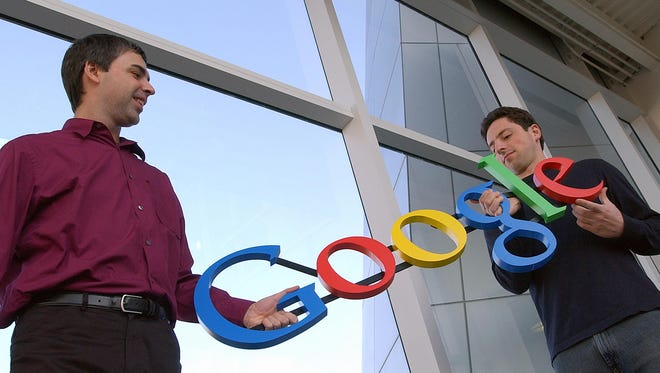 Google co-founders Larry Page, left, and Sergey Brin pose at Google headquarters in Mountain View, Calif.