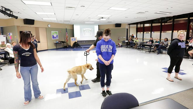Deanna Nanez, Carla Braungardt and Brooke Schwemer, all students at Moraine Park Technical College, line up to be sniffed for drugs by a Labrador during a demonstration of canine skills at the college. Milwaukee House of Corrections K-9 Officer Michael Rievera is the handler of the animal.
