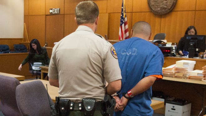 Joseph Salas, right, is handcuffed Aug. 21 to be transported back to the Ventura County Jail after a hearing in Ventura County Superior Court. Salas, 18, of Port Hueneme, was challenging his inclusion on an injunction against the Southside Chiques street gang in Oxnard.