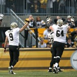 Nov 30, 2014; Pittsburgh, PA, USA; New Orleans Saints quarterback Drew Brees (9) celebrates a touchdown with tackle Terron Armstead (72) and tackle Zach Strief (64) during the second half at Heinz Field. The Saints won the game, 35-32.