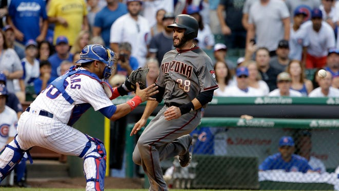 Arizona Diamondbacks' J.D. Martinez, right, scores on a single by Jake Lamb as Chicago Cubs catcher Willson Contreras waits for the ball during the eighth inning of a baseball game Thursday, Aug. 3, 2017, in Chicago.